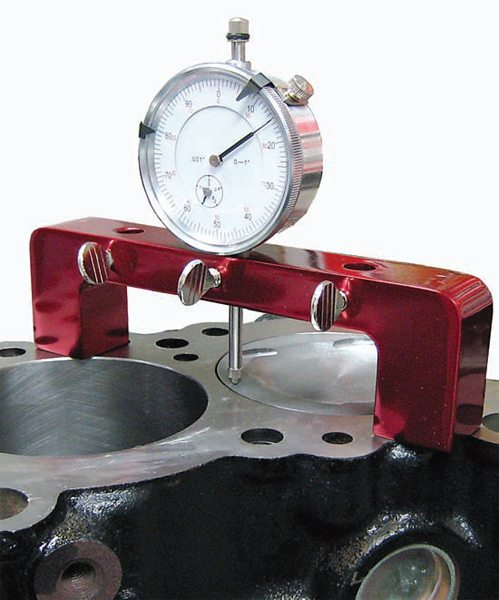 Use a dial indicator on a bridge stand to measure differences in parallel surfaces such as piston tops and cylinder block deck surfaces.