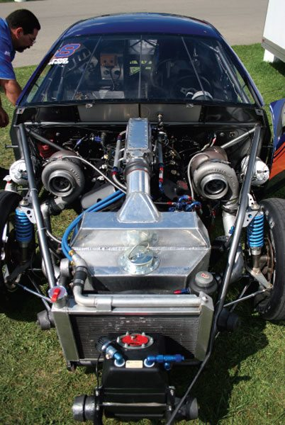 Manny Cruz of the Bronx, New York, uses a pair of Garrett GT42 turbos on his 3.0-liter V-6 Mercury Cougar, which races in the Pro Rear Wheel Drive Sport Compact class. The compressor outlet from each turbo is routed forward where they enter the aluminum cased water-to-air aftercooler (1), and from there, the aftercooler combines the air from both turbos into a single duct boost tube (2) that enters the engine's intake air plenum (3).