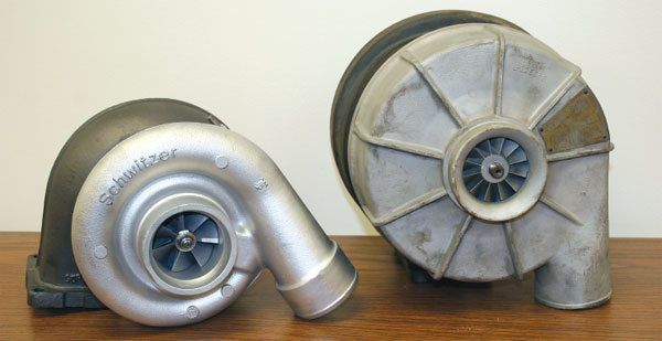 The current Schwitzer-BorgWarner model S3 on the left has a slightly higher airflow range than the older Schwitzer model made in the '60s for Cummins Engine Company. While the intended applications are different, it's easy to see the dramatic design differences that have come about from computer-aided designs, improved materials, and manufacturing processes. (Courtesy Diesel Injection Service Company, Inc.)