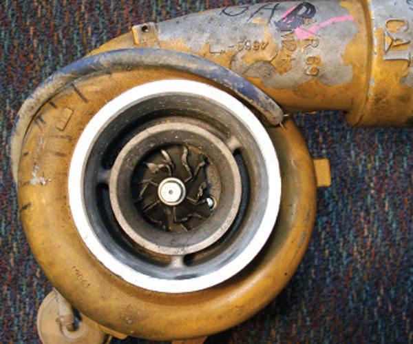 A turbocharger from a 550 hp Caterpillar engine model 3406E has obviously experienced a compressor wheel failure. The turbine shaft on this turbo actually broke due to the nature of the compressor wheel failure probably happening at very high speed and the imbalance caused a catastrophic failure. On initial inspection it appears like it may have been foreign object damage. However, note the compressor wheel blades have separated deep inside of the wheel, well past the inducer. The three ribs that are supporting the inducer ring are symmetrically spaced and caused a premature wheel failure due to wheel harmonics. The fix was a casting change that went to four support ribs asymmetrically spaced.