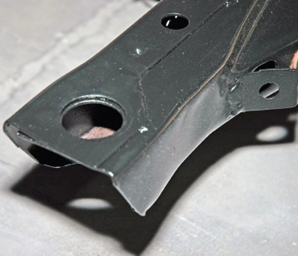 This is a clean and freshly powdercoated front subframe end. The large hole on top is where the body bushing goes.