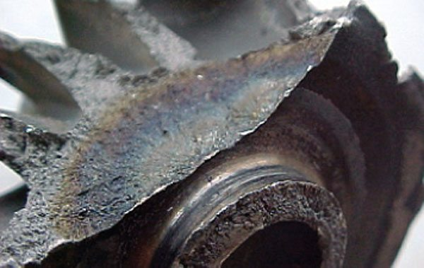 It is relatively rare to see a turbine wheel hub fracture, but when it happens it's usually a fatigue type of failure, or the unit has been operated under extreme temperatures. If the extreme temperatures are at fault there'll be additional signs such as blade tips that have thrown off material before hub fracture occurred. In this case, failure initiated in high stress area of back disc, but no defect is noticeable. A severe duty cycle may have caused this failure. (Courtesy Honeywell Turbo Technologies)