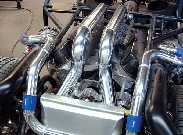 This twin turbo system utilizes all polished aluminum boost tubes to and from the aftercooler for a very nice look. Note the location of the turbochargers just behind the front wheels for hood clearance and weight distribution, and the much larger black air inlet ducting run parallel to the boost tubes leading from the compressor discharge to the aftercooler. (Courtesy Vibrant Performance)