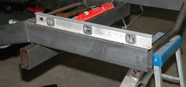 Here's the new frame section being fitted to the car. We have spirit levels on it to make sure it lines up with the rest of the structure, which we've already squared and leveled. We'll also measure from fixed points on the chassis to make sure everything is where it should be before we weld.