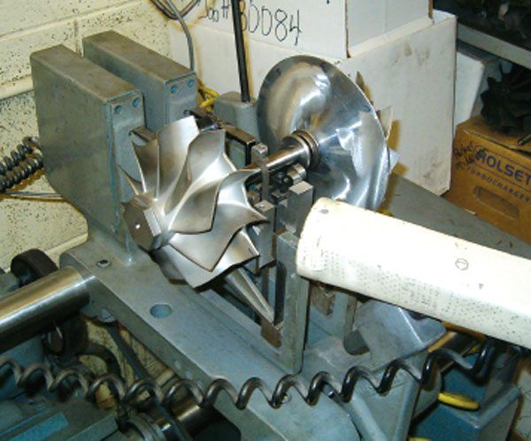 Here a rotor group is stacked-up and torqued, and then balanced before being assembled into the bearing housing. Prior to this step, each wheel was two-plain balanced as usual. The extra step to balance the entire rotor group is done since this assembly will be expected to live running speeds of around 150,000 rpm, which far exceeds the original design intent. (Courtesy Columbus Diesel Supply)