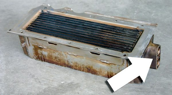 The core of the water-to-air cooler acts much like a radiator in reverse. Coolant is passed through the ports (arrow) at right while the compressed charge flows across the fins from the top. (Nate Tovey)