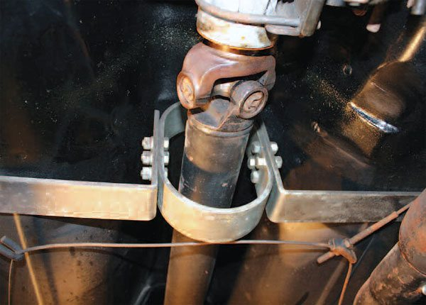 A typical, universal multi-piece driveshaft safety loop is made of four pieces that are bolted together: top and bottom semi-circles and two L-shaped side brackets. The loop is properly located on this Z-28, a few inches behind the front universal joint.