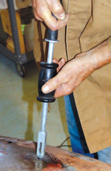 Once the stud is welded to the panel, a specialized slide hammer grips its shank. The stud is then slide hammered away from the panel, pulling out the low metal. The stud is then twisted or cut off, and the area is ground flat.