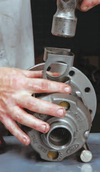 The preload S-spring can be com-pressed with channel-lock-style pliers or a C-clamp to help with installation. Once you have rebuilt several of these units, you develop the feel for how much to tap the spring to get it started in place.