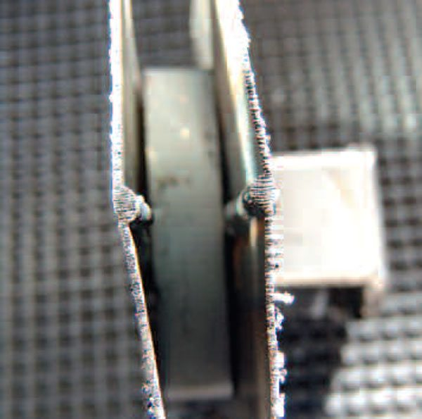 The best test for penetration is to cut through a weld, and look at its cross-section. Such a cut is shown here, with the bead tops facing each other. The lacerations in the cuts are the marks left by the band saw that separated the pieces.