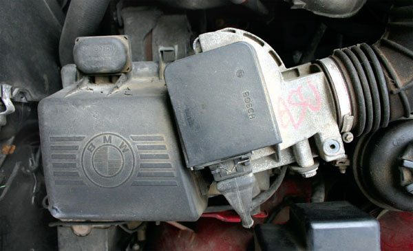 Vane Air Meter as installed in a 1990 BMW 3-series. Notice the curved balance chamber for the flapper door. This design still required significant temperature compensation to work properly. (Nate Tovey)
