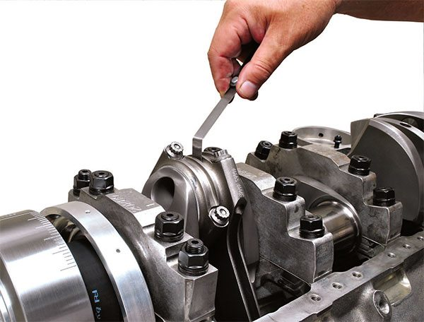 Proper rod-side clearance is essential to ensure adequate oil pressure and the integrity of the hydrodynamic oil wedge at the bearing. With too much clear¬ance, oil bleed-down is excessive and the wedge begins to lose its effective¬ness in supporting the crank in a film of oil. Too little clearance may result in undesirable contact between the crank face and the rod, and elevated oil temperature due to limited bleed-off from the bearings.