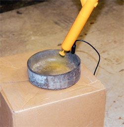 A simple cardboard box makes an effective stage for powder coating. You can use tables or anything, really, but the box can be taken outside, blown off, and reused indefinitely. Or you can simply recycle it when you're done.