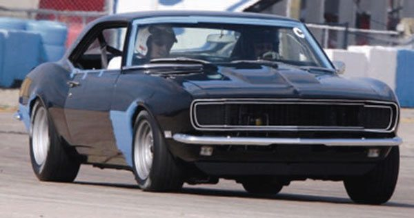 Here's the same car a few months later. The slapper bars are gone, and an SC&C Stage 1-Plus front suspension and Hellwig tubular front and adjustable-rate rear sway bar have been added. Seen here at Sebring's road race track at high speed, body roll is hardly discernable. The blue tape is to protect the paint from stone chips and to keep the windshield trim on at very high speeds. Dan experienced an obvious night-and-day improvement in handling with a few well-chosen bolt-on parts. (Photo Courtesy Dan Babb)