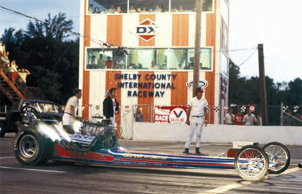 This beautiful shot of the Shreve Automotive AA/FD dragster seems to really set the mood for the late 1960s drag racing scene. The blown nitro Hemi is belching out flames as it rolls into the beams, while spectators eagerly await the launch. This shot also offers a great view of the new and improved tower. (Photo Courtesy LPC Photo, Larry Chambers)