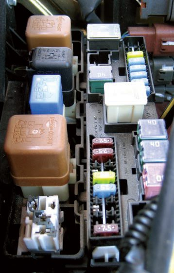 The underhood fuse box in the 2004 Nissan Frontier truck houses relays, fusible links, and fuses for those accessories that are tied to the battery directly. The box is located directly behind the battery.