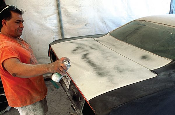 "The key to any great paint job is careful and thorough block sanding of the whole body, which is usually repetitious (prime, block sand, prime, block sand). The longer the sanding board or block the better, especially on large panels. Sanding without one is useless for getting panels straight. High-fill primers are a big help in this process, especially if you start with a ""guide coat"" on top. This is simply a dusting of a contrasting color of paint—spray can black is cheap and handy—wafted over the primer coat."