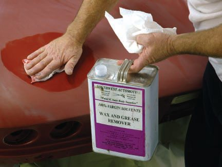 """No paint job—unless it's been stripped to bare metal and treated with an etching agent and/or sealer—should be started without a thorough cleaning with a """"wax and grease remover"""" or better yet, a """"Silicone Remover,"""" as shown. Silicone wax is a painter's nemesis; don't use it. But any wax, oil, road tar, etc., should be cleaned off the surface before you do anything else (sanding just embeds it). Then, just before color coats, clean it again (being sure to wipe it off before it dries, as directed), because hand oils, or even sweat drops, can lead to fisheyes in the paint."""