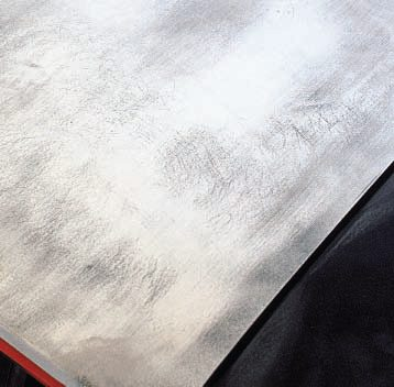 In this example on a flat deck lid with a good coat of high-fill primer, a quick sanding with 80-grit on a long board quickly shows bare high spots, dark low spots, and sand scratches.