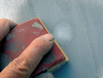 When it's hardened, sand both the putty and the primer level with 180-grit on a small block, as shown.