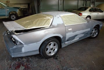 This is how the car looked before it went in the spray booth. You can see it's well-sanded and there wasn't a lot to mask (the whole masking job took about 15 minutes). They wouldn't let us in the booth to take pictures, but you can see it in the background. It's actually a spray booth attached to a separate drying/heating booth. The painter mixed the base coat from toners in the shop to the formula for the color code of the car.