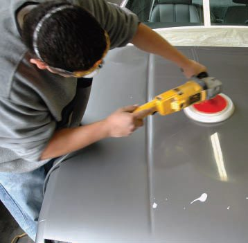 """We'll talk much more about the color sand and rub out process in Chapter 11, and it is pretty unusual for a one-day type paint shop to offer this option. But, as we say in the text, if they know they have to sand and rub it, they'll be sure to put enough paint on. Here the """"buff guy"""" adds a minimal amount of compound from a plastic squirt bottle, then quickly brings up a gloss with the power buffer on the hood. The whole sand-and-rub took about half a day."""