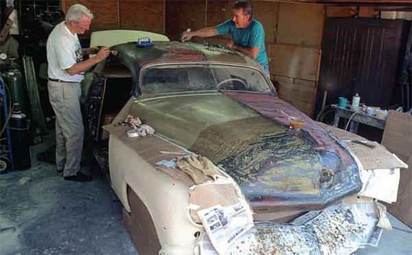 """The only practical way to strip layers of paint off your car at home is by using a brush-on/scrape off liquid stripper. Don't get the kind at the hardware store; go to your automotive paint dealer and get the very strong type made for cars, which is usually called """"aircraft stripper.""""  The job is tedious, very messy, and potentially dangerous. It also helps to have friends pitch in, as Jim McNeil is doing here while they begin to scrape 40 years' worth of paint off the famous Hirohata Merc Barris custom in Jim's garage. Note paper, cardboard, and boxes to collect the noxious drips and scrapings."""