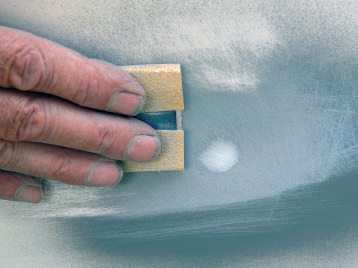To sand the putty smooth, I wrapped a piece of 80-grit paper around a flat, hard rubber squeegee as a sanding block. Once it's smooth, re-prime the area before painting.