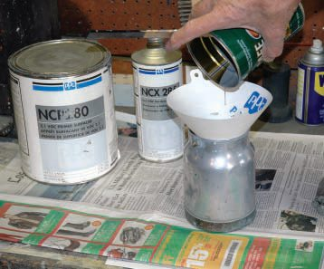 The reason you need a separate mixing container is so you can thoroughly mix the components with the stirring stick, but more importantly so that you can strain this mixture as you pour it into the spray gun pot. Never mix paint in the gun without straining.