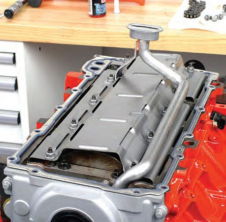 If the pump is located far from the sump, the tube will be long and require at least one additional support bracket to support the weight and length of the pickup tube. It is usually fastened to a main cap bolt or stud. Here is a stock type pickup on a GM LS engine. The sheet-metal tray seen here serves as a windage tray, which protects the crankshaft from oil splashback from the pan. This reduces parasitic oil drag on the crank counterweights and rod big ends.