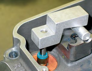 With valvespring removed, the standheight checker drops over the valve stem, while the opposite end rides on a checker shaft that rests in the rocker stand shaft groove. The checker allows you to dial in correct rocker arm geometry. The valve stem tip should be flush with the upper surface of the checker. If the valve tip is lower (below flush with the checker), correction means moving to longer valves or milling the head's shaft stand bosses. A quicker, easier, and cheaper fix is to use the proper-thickness valve lash cap. If you're using titanium valves that don't already have hard tips, you need lash caps anyway. If the valve tip sits too high (above flush with the checker), shimming the rocker shaft stands is required.