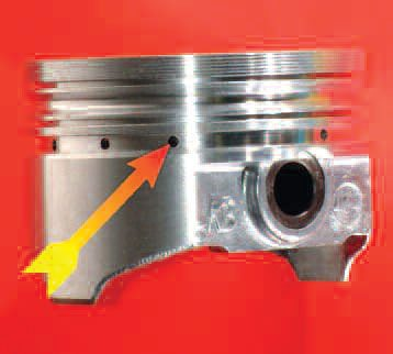 Street-oriented pistons often have a slot instead of the preferred drilled holes as seen here. The slot acts as a heat dam to cut skirt expansion, but weakens the piston.