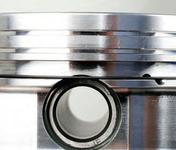 Here's an example of a piston that requires a support rail for the oil ring. Note, because of the short compression distance, that the wrist pin bore intersects with the oil ring groove. After installing the rod to the piston, install the support rail to the floor of the oil ring groove.