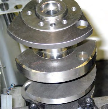 If it's necessary to add weight to a counterweight, it can be done at the edge or at the face. If weight is added to the outer edge, it's necessary to tackweld the weight in place to eliminate the possibility of it being slung outward. If weight is added to the face, a press-fit is adequate. Because of the required location of the weight shown here, the rear weight was drilled to access the target counterweight for drilling. A heavy-metal slug (tungsten, also known as Mallory metal) is press-fit into the target hole. Again, the technician refers to a chart specifying the diameter and length of tungsten required for a specific weight factor (in grams).