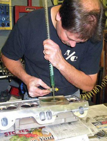 A burette makes it easy to measure combustion chamber volume. This is done by installing the valves (with a light smear of lithium grease on the valve faces) and a spark plug to provide a liquid seal. A clear plexiglass plate with a drilled hole is adhered to the deck with grease. Colored liquid is introduced from the burette, while monitoring the volume of liquid (in cubic inches) required to fill the chamber. The volume of each chamber is recorded and compared. The chamber with the largest volume can be used as the zero point of reference. Material may then be removed from other chambers or by sinking the valves deeper to create a matched equal-volume set of chambers.