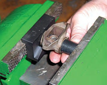 Using the Summit kit's presser (black piece) push the bearings and trunnion out of the rocker. The presser has a shallow counterbore that aligns with the stock bearing. Summit's specialty fixture is shown on a bench vise. Push the old trunnion completely out of the rocker along with both OEM bearings.