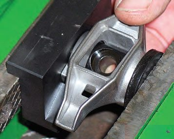 Using a bench vise with Summit's specialty fixture to secure the opposite side, press the remaining bearing into the rocker, so that the outer face of the bearing is flush with the outer surface of the rocker body. Apply a bit of engine oil to the outside of the new bearings to ease press-in.