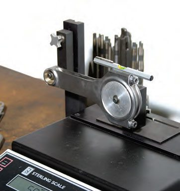 Each component (rods, rod bearings, pistons, pins, locks, and rings) is weighed on a precision digital scale. The first step is to place the weight of the on-scale stand on the scale and tare the scale. This will return the scale reading to zero with the bare stand to remove the weight of the stand from the equation. When weighing a rod big end, the rod must be mounted with the bore centers horizontal and parallel (note the bubble level on the rod big end). The small end is supported on a stand off the scale, while the big end is supported on a stand that rests on the scale.