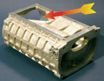 The form of the case discharge into the manifold has also been refined greatly. The discharge port shape (arrow) is no longer a straight slot, but a shape to compliment the rotor compression characteristics.