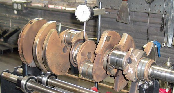 Crank runout is performed by resting the crankshaft on smooth V-blocks or rollers. A dial indicator is located at the center main journal and the crank is slowly rotated while monitoring the gauge.