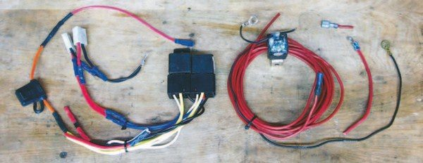Fig. 2.29. The fan relay is on the left. Note the pair of mismatched relays in pre-assembled 14 AWG (too small!) sockets, a plethora of butt connectors, and the 18 AWG (way too small!) ground leads for the fans. The fuel pump relay wiring is on the right. Note the green corrosion on the relay; it was mounted upside down and got wet. Also note the 14 AWG wiring to the pump and 18-gauge pump ground. Man, oh man, this is among the worst jobs I've ever seen.