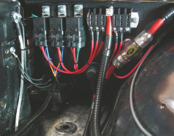 Fig. 2.31. I fabricated a power center of ABS plastic to fit inside the passenger-side fender (see also Figure 4.8 on page 61). The power center contains waterproof relays for the fans and fuel pump (wired with 10-AWG TXL), an ATC fuse panel, the fuse holder for the audio system, and a junction stud to connect the power feed for the wiring harness. Note the upgraded grounding to the core support. Clean, orderly, and serviceable.
