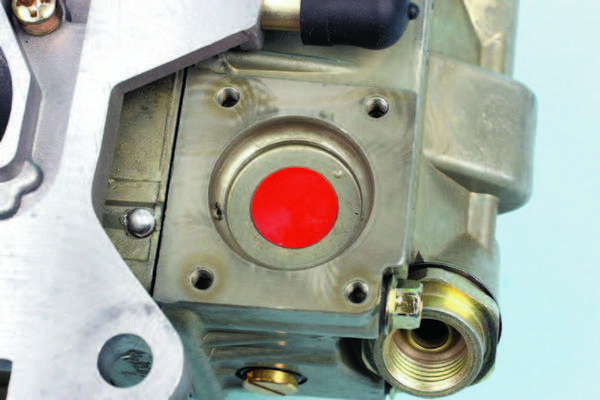 "This orange ""dot"" indicates the rubber/silicone umbrella-style check valve. This style, in contrast to the older check ball approach, seals with very little pressure, and moves from the sealed position when fuel is drawn into the accelerator pump cavity. Unless it's leaking, don't disturb it."