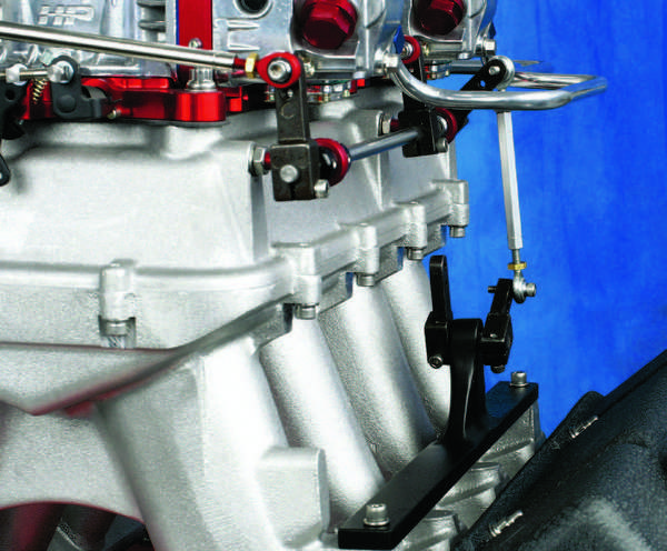 A bellcrank is the pivot base where the throttle cable (or rod) connects and transfers movement to the carburetor linkage. This must be mounted rigidly, as shown on this custom build; the base is secured to the intake manifold.