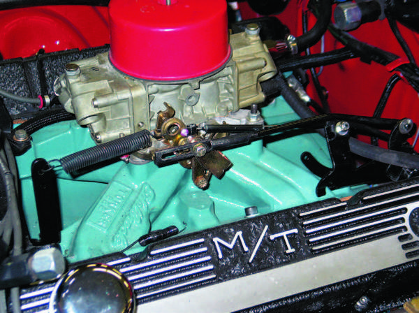 Here, the throttle linkage is being adjusted on a 1968 Mopar, using the original throttle cable and transmission kickdown linkage rod system. Note the return spring that pulls the throttle closed. Certain automatic transmissions, such as the Chrysler TorqueFlite, require careful rod adjustment at the carburetor throttle lever.