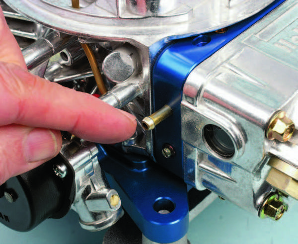 The 1/8-inch timed vacuum fitting for connection to a vacuum advance distributor is located on the passenger's side of the primary metering block. If you don't need vacuum advance, plug this fitting with a rubber cap.