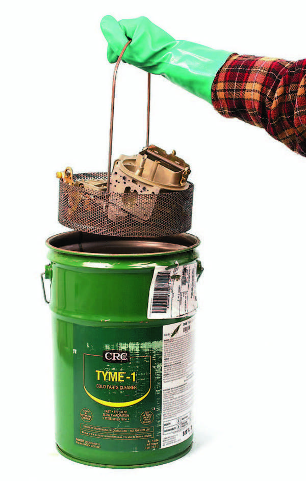 Load the carb parts in a parts cleaning basket. Although many small parts can be placed in the basket including jets, screws, sight plugs, and so on without fear of losing them, extremely small parts such as C-clips, pin clips, etc. are better cleaned by hand. Always wear chemical-resistant gloves and eye protection. Lower the basket into the solvent bucket slowly to avoid splashing. Leave the basket submerged in the solvent bucket for about 20 minutes. After removing the basket, rinse all parts with hot water and blow-dry with compressed air. When blowing compressed air into the throttle body, remember to adjust your compressor to approximately 25 psi before blowing air into passages inside the main body.