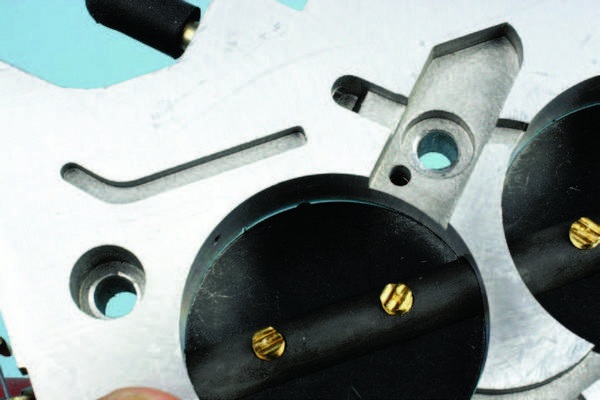 Notice the small gap at the edge of the throttle plate in relation to the throttle bore. This is normal. A gap to keep the primary throttle plates slightly open is set at the factory to aid in engine idle at closed throttle. Depending on carb model, this gap may be in the range of .010 to .015 inch. Do not attempt to modify the gap to fully seat the throttle plates.