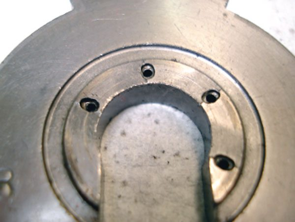 A view of the positive side of a thrust bearing reveals significant wear. In such a case it is also possible to see little or no wear on the negative side of the thrust bearing. There is a hardened thrust ring, or in some models a thrust collar that thrusts against the bearing at this point. These parts may not show much wear because they are significantly harder than the softer bronze material of the thrust bearing. (Courtesy Honeywell Turbo Technologies)