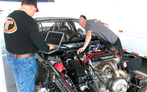 Harry Hruska, president of Precision Turbo and Engine, left, adjusts the Big Stuff 3 system in Stephanie Eggum's NHRA Sport Compact Hot Rod record holder.